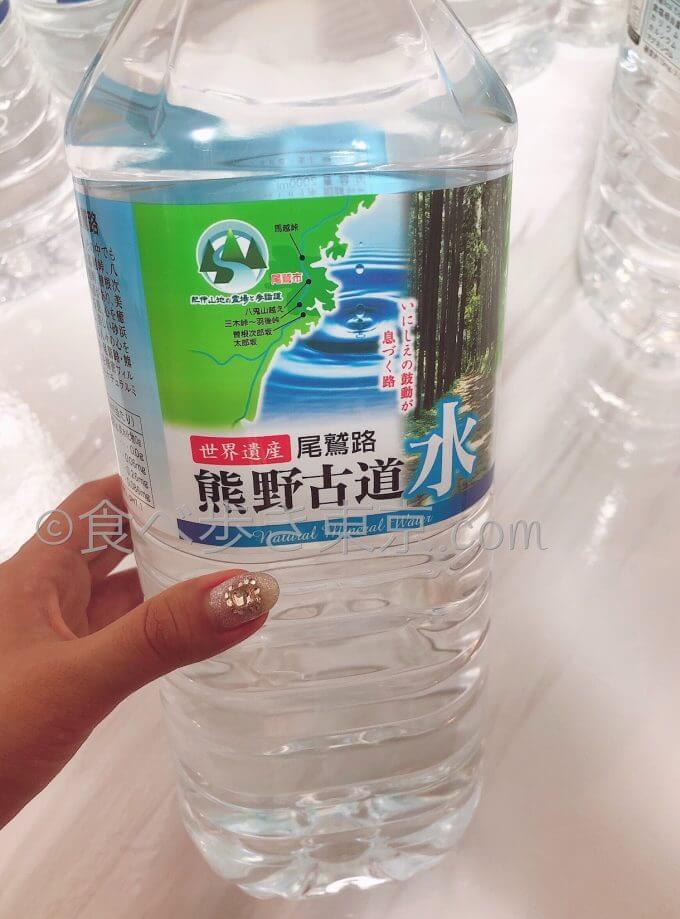 ミネラルウォーター熊野古道水を手に持っている